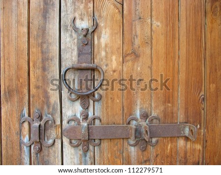 Ancient wooden door rustic metallic door handle detail - stock photo