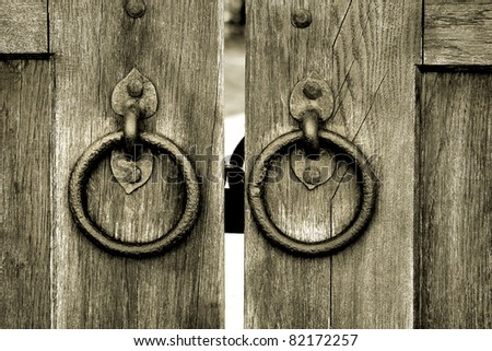 ancient wooden gate with two door knocker rings close-up - stock photo