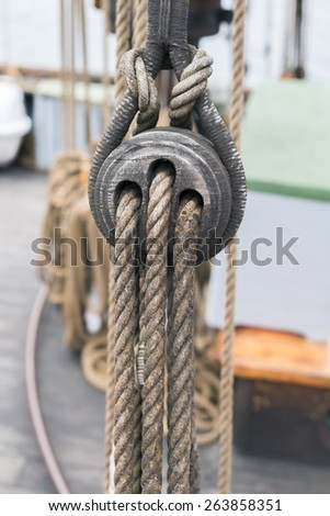 Ancient wooden sailboat pulleys and ropes detail - stock photo