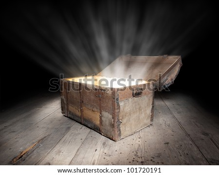 Ancient wooden treasure chest with the strong glow from inside. - stock photo