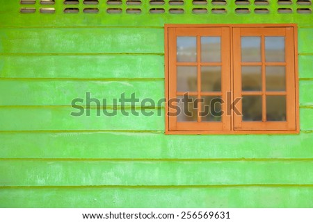 ancient wooden window with green wall - stock photo