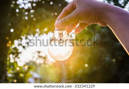 and holding a light bulb with sunset power concept - stock photo