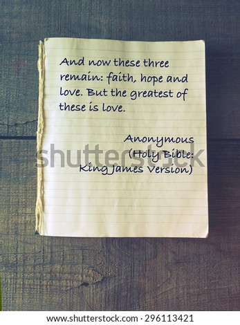 And now these three remain: faith, hope and love. But the greatest of these is love. Holy Bible. Vintage exercise book on wooden background - stock photo
