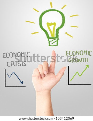 and pointing to the hand draw light bulb with falling and rising graph for economic crisis or growth concept - stock photo