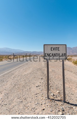 """Andean road with a Spanish traffic sign warning to """"avoid using high beam"""" - stock photo"""