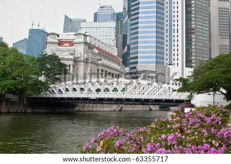 Anderson bridge in Singapore with The Fullerton Hotel on background.