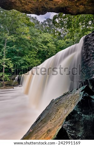 Anderson Falls, a beautiful wide waterfall in Indiana's Bartholomew County, is photographed from below a large rock overhang at one end. - stock photo