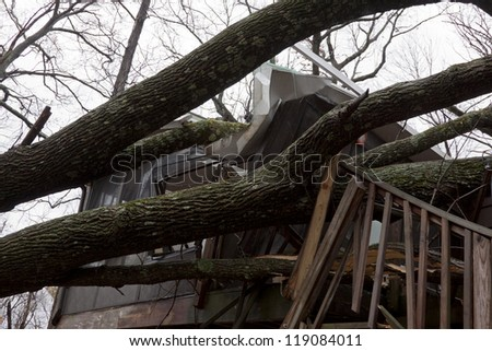 ANDOVER, NJ - OCT 30: Trees lay across the sundeck of a home after Hurricane Sandy made landfall in the northeast region of the US in Andover, New Jersey on October 30, 2012. - stock photo