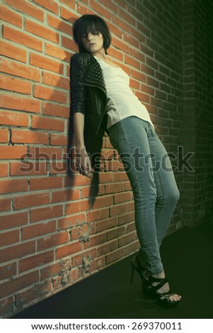 Androgyny female model in Heroin chic style near brick wall. Old style tinted image