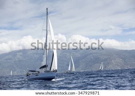 ANDROS - SYROS, GREECE - CIRCA MAY, 2014: Sailboats participate in sailing regatta 11th Ellada 2014 among Greek island group in the Aegean Sea, in Cyclades and Argo-Saronic Gulf.