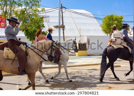 ANDUJAR,SPAIN - September, 6: men women and children involved walking on their mounts during the famous fair of the Andalusian horse on September, 6, 2014 in Andujar, Spain - stock photo