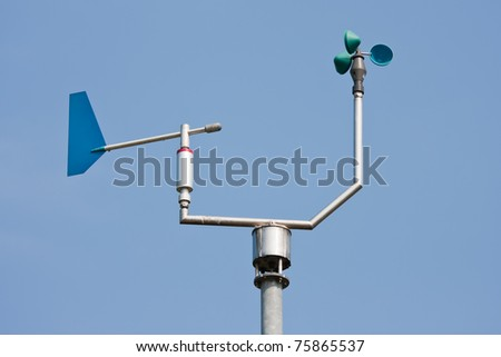 Anemometer measuring wind speed and direction with a blue sky in the background - stock photo