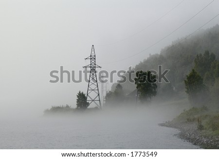 Angara River in Siberia, Russia, in the morning fog with power line towers - stock photo