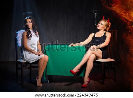 Angel and devil at dark room - stock photo