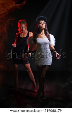Angel and devil on dark background - stock photo