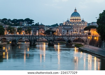 Angel bridge and St. Peter's Basilica copula in Rome, Italy during sunset