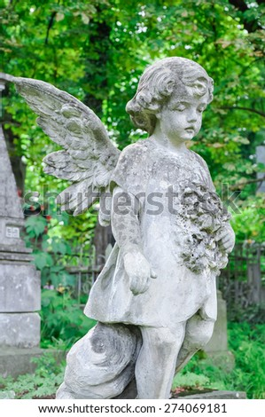 Angel child statue in the cemetery  - stock photo