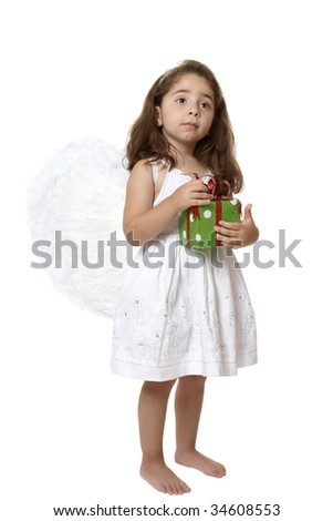 Angel girl wearing white embroidered dress and feathered wings is holding a red and greed present.