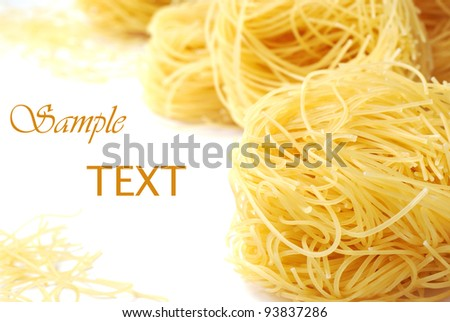 Angel hair pasta nests on white background with copy space.  Macro with shallow dof. - stock photo