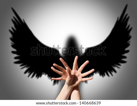 Angel, hand shadow like wings of darkness - stock photo