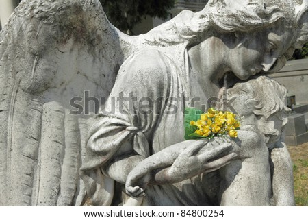 angel holding a child, antique sculpture on Monumental Cemetery of Staglieno, Genoa,Italy, Europe - stock photo