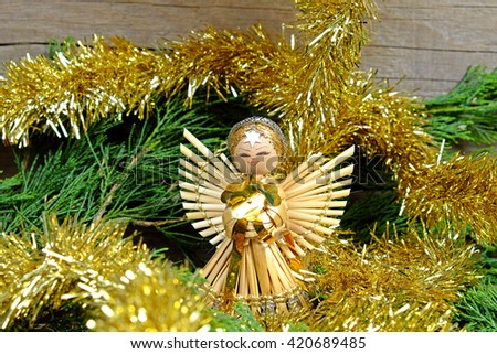 Angel made of straw with a star on his forehead for him christmas chain in gold color on old wooden table with green needles - stock photo