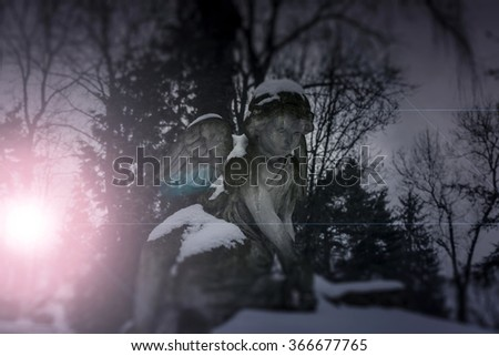 Angel statue illuminated by moonlight. Cemetery during the winter - stock photo