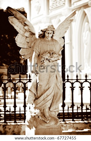 Angel statue on a cemetery in golden tones - stock photo
