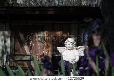 Angel Statue Surrounded by Purple Irises - stock photo