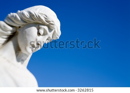 angel statue watching over a grave at an old cemetery, closeup against clear blue sky. shot with a lensbaby for optical blur.