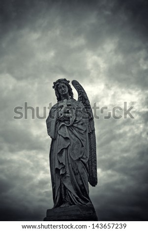 Angel statue. Weathered stone graveyard monument of an angel. - stock photo