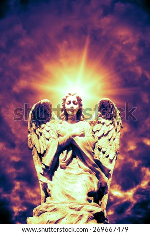 angel statue with flare behind it - stock photo