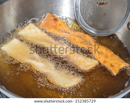 Angel wings are a traditional sweet crisp pastry made out of dough that has been shaped into thin twisted ribbons, deep-fried and sprinkled with powdered sugar. - stock photo