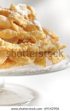 Angel wings are a traditional sweet crispy pastry made out of dough that has been shaped into thin twisted ribbons, deep-fried and sprinkled with powdered sugar. - stock photo