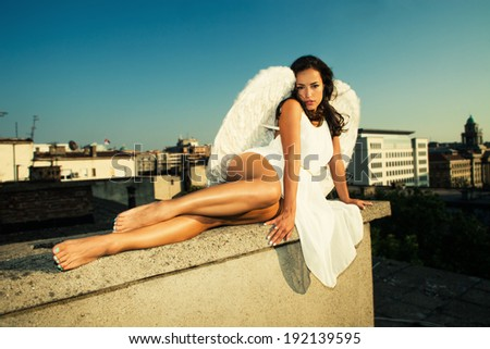 angel woman on building roof, summer day, Belgrade, Serbia - stock photo