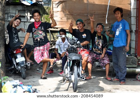 ANGELES CITY, PHILIPPINES - OCTOBER 9, 2012: Young unidentified filipino men posing at the garage area.