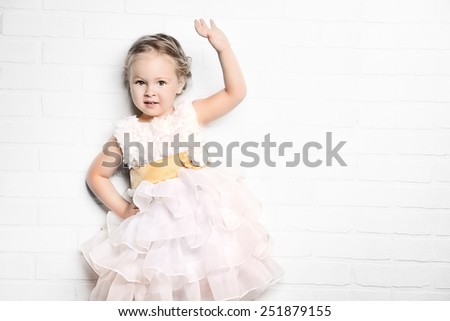 Angelic little girl in a beautiful white dress standing by the white brick wall. Childhood. - stock photo