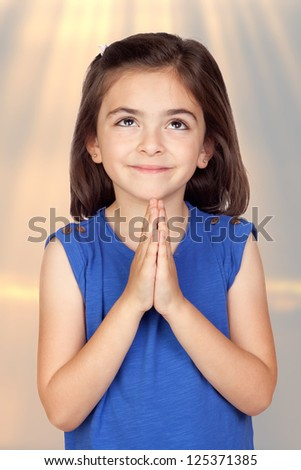 Angelic little girl isolated with a ligh of background - stock photo