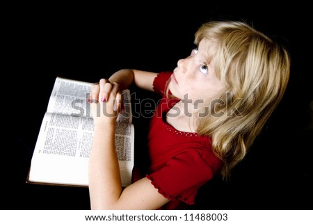 Angelic little girl saying her prayers over an open New Testament. - stock photo