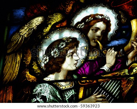 Angels are playing on instruments on a lead-glass of a basilica