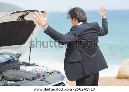 Anger businessman looking at engine of his car - stock photo