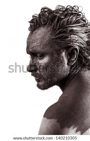 Anger, Dreaming, man covered in mud, naked, in profile, dirty skin - stock photo