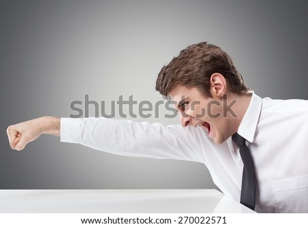 Anger. Furious businessman throws a punch into the computer - stock photo