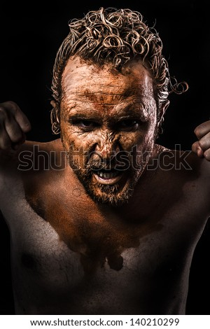 Anger man, Warrior young covered in mud - stock photo