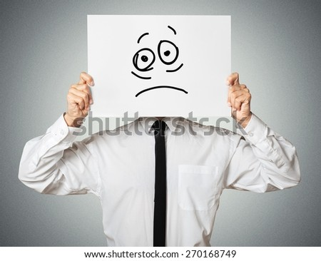 Anger. Young businessman holding card with a angry face on it isolated on gray background - stock photo