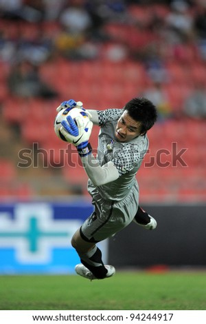 ANGKOK THAILAND-JAN18: S. Hathairatanakool (GK) of Thailand (yellow) in action during the 41st King's cup  between Thailand and Norway at Rajamangala stadium on Jan18,2012 in Bangkok,Thailand. - stock photo