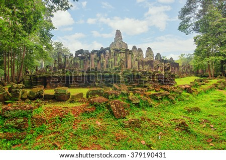 Angkor Wat - a giant Hindu temple complex in Cambodia, dedicated to Lord Vishnu. Trees in ruin Ta Prohm, part of Khmer temple complex, Asia. Siem Reap, Cambodia.