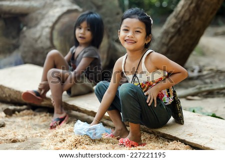 ANGKOR WAT, CAMBODIA, DECEMBER 06, 2012: Two Cambodian little girls are sitting near the temple for selling some souvenirs to tourists in Angkor wat, Siem Riep, Cambodia - stock photo