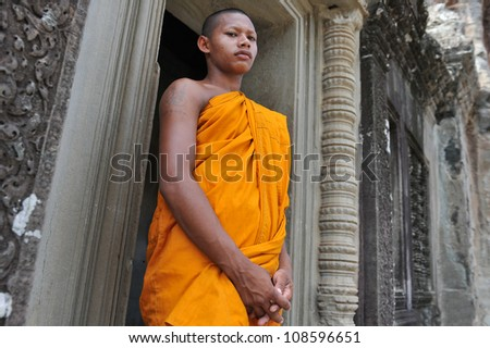 ANGKOR WAT - JULY 11: A Buddhist monk waits for alms on July 11, 2012 in Angkor Wat, Cambodia. There are estimated to be over 50,000 Buddhist monks in Cambodia, with 97% of the population Buddhist. - stock photo