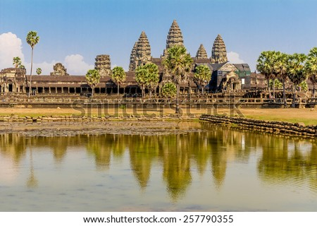Angkor Wat seen across the lake, reflected in water - stock photo